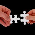 Hände mit Puzzle-Teilen